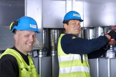 Två glada arbetare som installerar ventilation