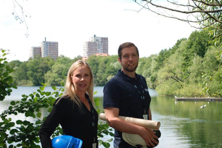 Två arbetare står vid en sjön